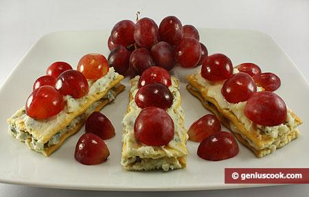 Закуска на крекерах с сыром Горгонзола и виноградом