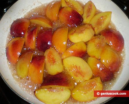 Персики жарятся в сливочном масле с сахаром