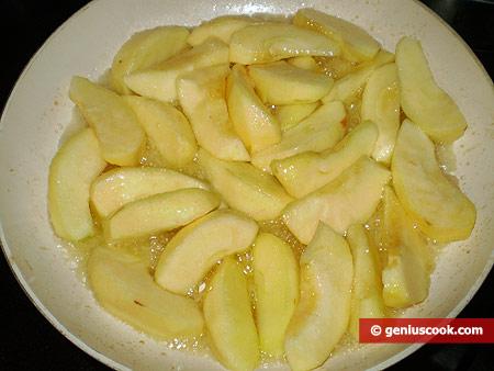 Яблоки жарятся на сковороде