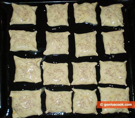 Пирожки смазаны яйцом и посыпаны кунжутом