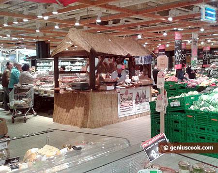 В центре магазина кибитка фермера. Он ножом нарежет прошутто тоненько.